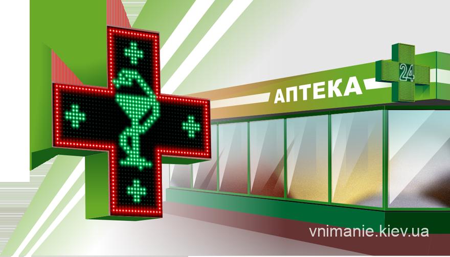 Аптечный красно-зеленый LED крест на фоне аптеки